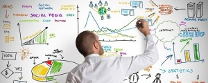 Man drawing marketing metrics on a whiteboard.