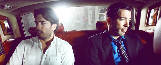 Jonathan and Drew Scott in rear seat of a car.