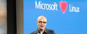 """Microsoft CEO Satya Nadella appears in front of a """"Microsoft loves Linux"""" projection."""