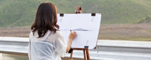 female artist draws landscape