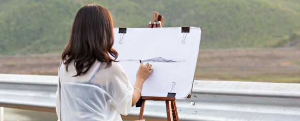 Young artist sketching a landscape, focus on hand