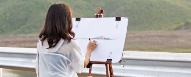 female artist draws landscape