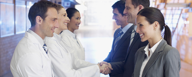Business people shaking hands with scientists in factory