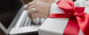 White Gift Box with Red Ribbon and Bow Near Man Typing on Laptop Computer.